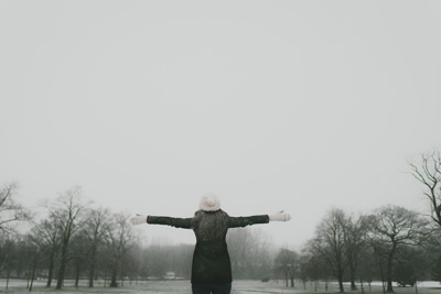 Woman with arms outstretched on a grey winter day