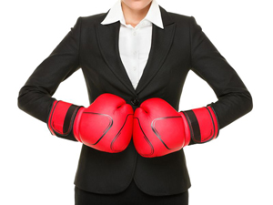 Woman at work with boxing gloves on to represent fighting-fit