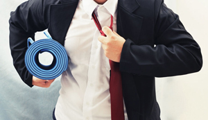 Man at work with yoga mat taking off his tie